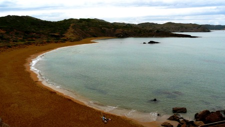 menorca: A lonely couple relaxing on a cloudy day in Cavalleria Beach in Menorca, Balearic Islands, Spain.