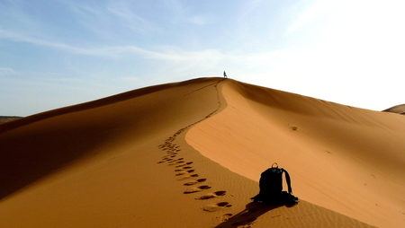 travel destinations: Detail of back and hiker climbing to the top of the Great Sand Dune in the red dune sea of Erg Chebbi, Morocco Stock Photo