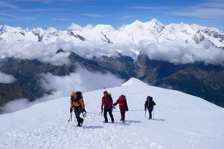 four peaks wilderness: The Alps, Switzerland - July 12th of 2007: Climbers reaching  Weissmies mountains summit 4,017m. - 13,179ft. a Pennine Alps peak in the canton of Valais near the village of Saas-Fee. Editorial