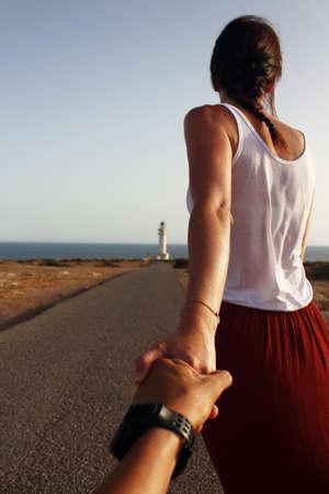 despacio: hermosa mujer joven que camina lentamente al faro de Cap de Barberia durante una puesta de sol del verano increíble.