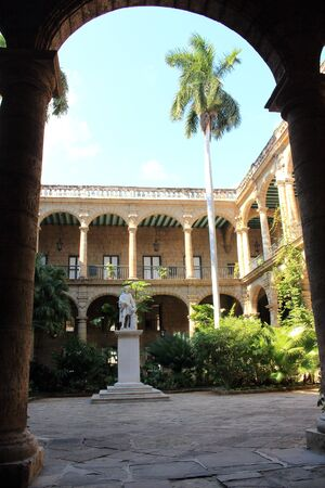 exuberant: Main entrance of the ancient spanish government palace in Old Havana with a statue of Christopher Columbus and exuberant tropical garden.