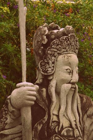 mystic place: Lonely guardian statue placed in a garden of the Imperial Grand Palace in Bangkok, Thailand