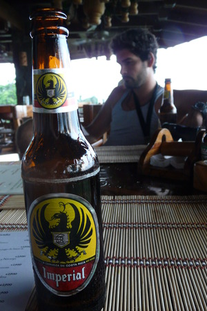 manuel: Manuel Antonio, Costa Rica - August, 28, 2010: Tourist drinking an Imperial lager. This brand of beer, manufactured by the Florida Ice & Farm Company was first produced by the Ortega brewery in 1924. Editorial