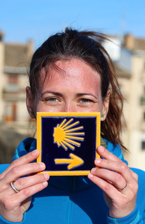 Young beautiful female pilgrims portrait posing with the typical Camino de Santiago blue  tile painted with a yellow shell and arrow.