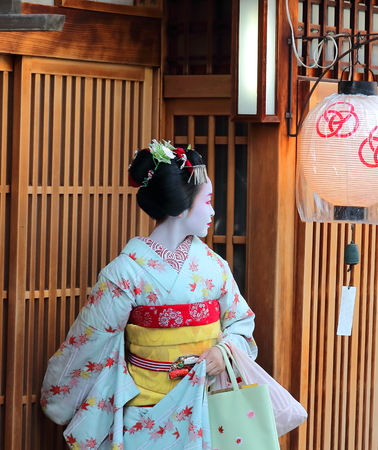 Kyoto, Japan - August, 11th of 2017: A maiko leaving a tea house in Miyagawacho neighborhood. Centuries ago, these female entertainers were so popular, but a few hundreds can be found now in Japan.
