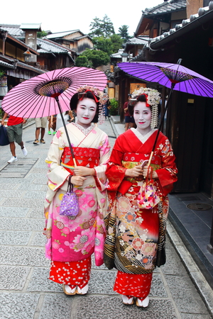 Kyoto, Japan-August, 11th of 2017: Young Japanese girls dressed in geisha's custom taking a walk in the stone-paved roads of Ninenzaka and Sannenzaka that lead up to the World Heritage Kiyomizu Temple