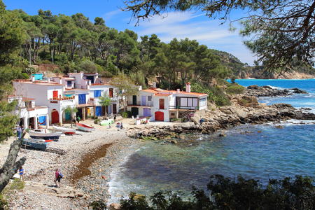 Main view of cala sAlguer, a lovely beach surrounded by traditional fishermens white buildings with colorful doors and windows, Palamos, Costa Brava, Spain. Editorial