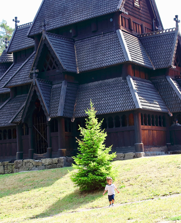 Little two years old boy running and playing in front of the Gol Church,  a stave church originally built in Gol city, but now located in the Norwegian Museum of Cultural History at Bygdoy in Oslo, Norway
