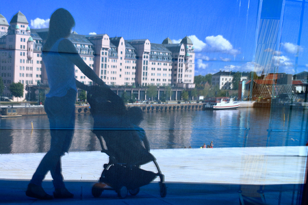 A young mother reflected on the Oslo opera building glass wall with her little baby relaxing in his baby carriage, Oslo, Norway.