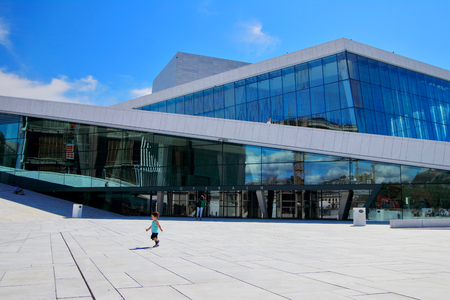 Cheerful little boy runs in front of the Oslo opera building during a sunny summer morning, Oslo, Norway.