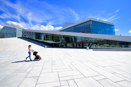 A young mother enjoying a walk through the Oslo opera building with her little baby relaxing in his baby carriage, Oslo, Norway.