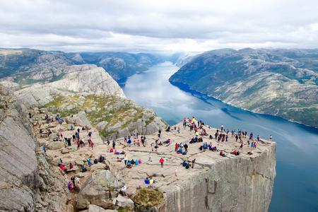 Several hikers enjoying the views in the summit of the Pulpit Rock (Preikestolen), one of the world's most spectacular viewing points . A plateau that rises 604 meters above the Lysefjord, Norway. Editorial