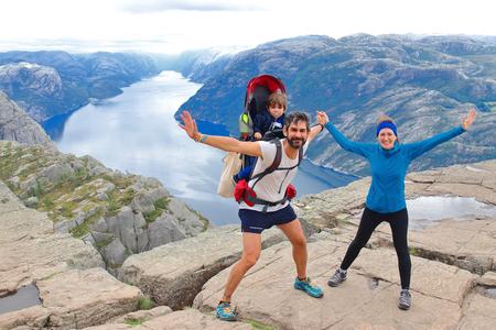 Una coppia allegra e il loro bambino in cima al Pulpit Rock (Preikestolen), uno dei punti panoramici più spettacolari del mondo. Un altopiano che si erge a 604 metri sopra il Lysefjord, Norvegia.