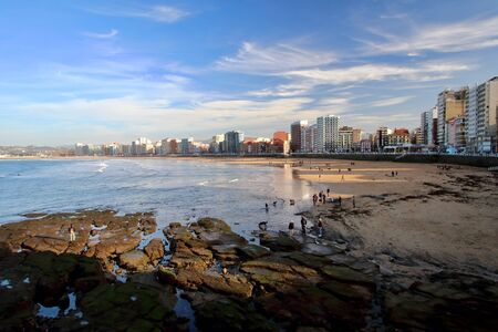 Main view of San Lorenzo beach with Gijon downtown on background during a sunny Easter evening, Asturias, Spain.