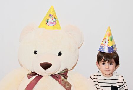 Two years old little boy and his teddy bear best friend wearing birthday hats and posing in front of the camera before kids birthday party.