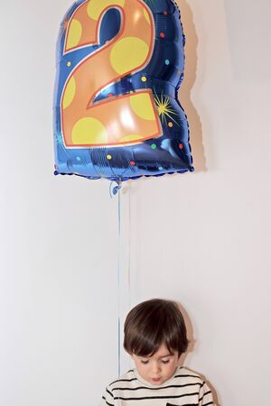 Two years old little boy holds a balloon on his birthday party. Stock Photo
