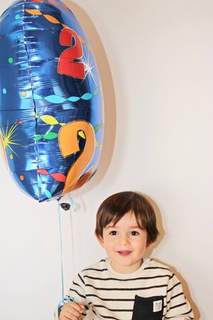 Two years old little boy holds a balloon on his birthday party. Reklamní fotografie