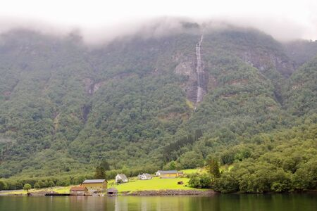 Main view of Styvi village and its farm museum with surrounding waterfalls on background. This tinny village is located on the western shore of the Naeroyfjord, north of Gudvangen village, Norway.