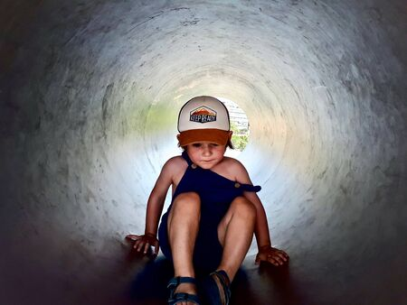 Portrait of a cute two years old little kid playing inside a metal tunnel on an outdoor adventure park in Barcelona, Spain.