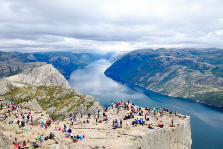 Several hikers enjoying the views in the summit of the Pulpit Rock (Preikestolen), one of the worlds most spectacular viewing points . A plateau that rises 604 meters above the Lysefjord, Norway. Editorial