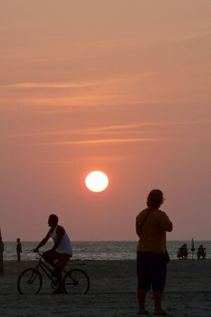 Several young people enjoying an amazing sunset in the main beach of Jericoacoara, Brazil.