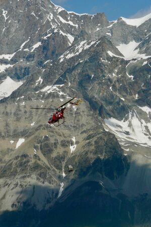 Rescue helicopter in action in the swiss alps close to Matterhorn and Breithorn peaks, Zermatt, Switzerland. Editorial