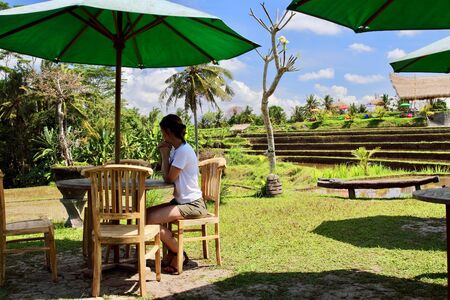 A beautiful young woman relaxes on a warungs terrace close to typical rice paddies after a trek under the sun in the Campuhan ridge walk, Ubud, Bali. Stok Fotoğraf