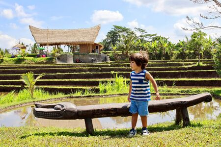 A cute little kid posing in front of the camera with the rice paddies close to Campuhan ridge walk on background, Ubud, Bali.