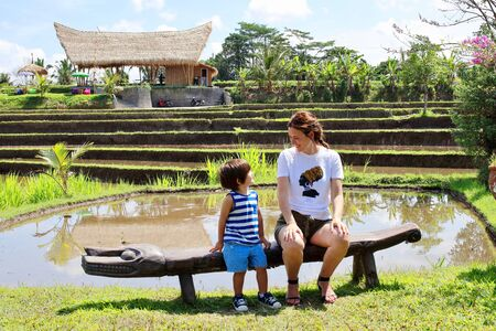 A cute little kid and his mum enjoying their time posing in front of the camera with the rice paddies close to Campuhan ridge walk on background, Ubud, Bali.