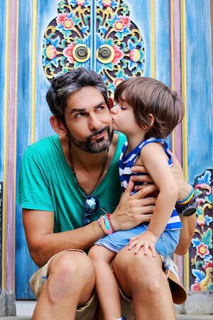 Portrait of father and his cute little kid posing in front of the camera with a colorful door of a typical Indonesian house on background, Ubud, Bali.