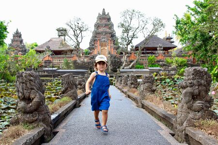 Cute little kid running and having fun in Pura Taman Saraswati temple, Ubud, Bali, Indonesia. Reklamní fotografie