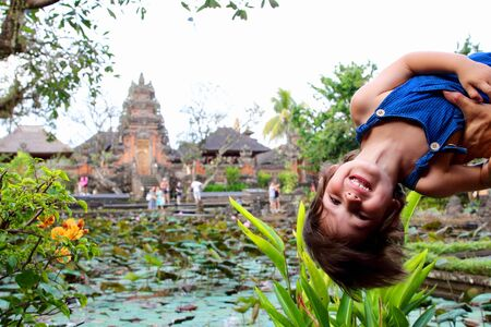 Portrait of a cute little kid with Pura Taman Saraswati temple on background, Ubud, Bali, Indonesia.