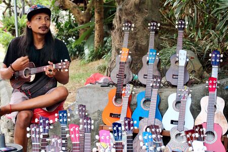 Young Indonesian vendor playing the guitar in his souvenirs street shop in JL Monkey Forest road, close to well known Ubud street market, Bali Editorial