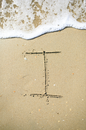 Letter drawn on the sand beach