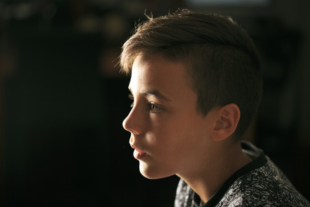 Boy with green eyes looking at the television Stock Photo