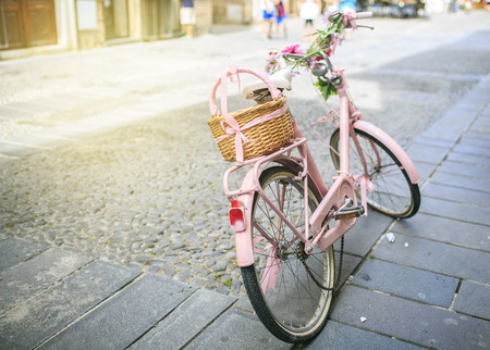 vintage Pink bicycle with basket of flowers Stock Photo