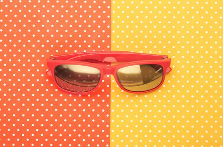 Orange sunglasses with colorful topped background
