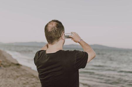 Uomo sulla spiaggia che fa una chiamata a