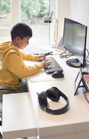 Boy with yellow t-shirt in the computer making homework