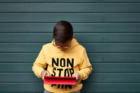 Boy with yellow sweatshirt surfing with his tablet . Wooden green Background