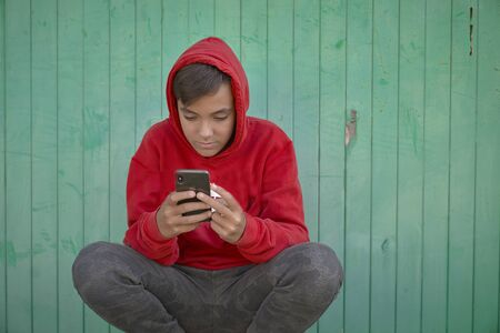 Boy with red sweatshirt surfing with his smart phone . Green Background Banco de Imagens