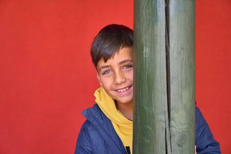 Green eyes kid with red background smiling Banco de Imagens