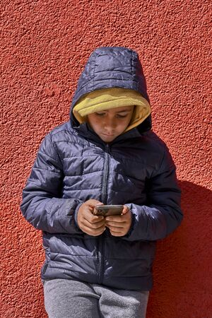 Boy with yellow sweatshirt surfing with his smart phone . Red Background