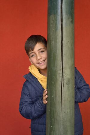Green eyes kid with red background smiling Imagens