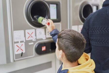 Child recycling plastic bottles in a machine