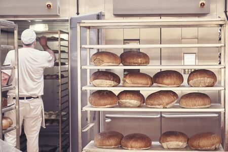 Man baking bread in the bakery Imagens