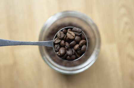 Spoon of coffee with bur background Imagens