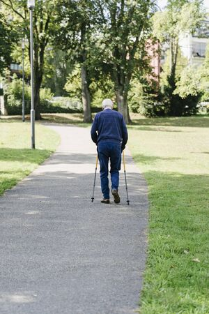 Older man walking with canes in the park