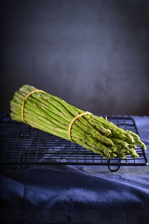Fresh green asparagus on wooden table background. Healthy lifestyle concept.