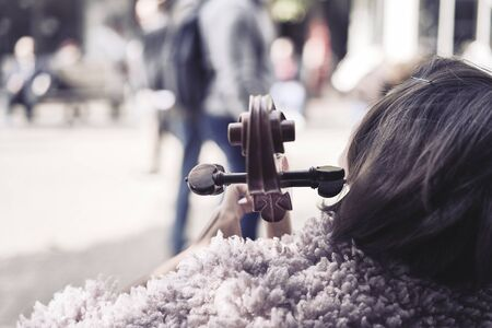 Musician woman playing cello in the street